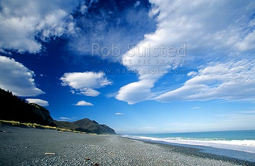 Dramatic cloud formations over a secluded beach on the Kaikoura Coast, Kaikoura, Kaikoura District, Canterbury Region, New Zealand (NZ) stock photo.