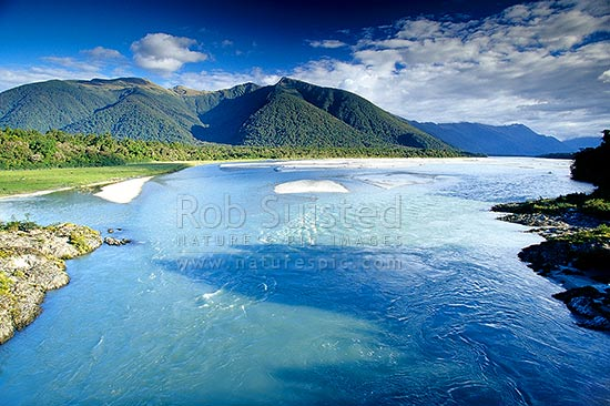 The mighty Arawhata River with the Haast range at left, South Westland, Westland District, West Coast Region, New Zealand (NZ) stock photo.