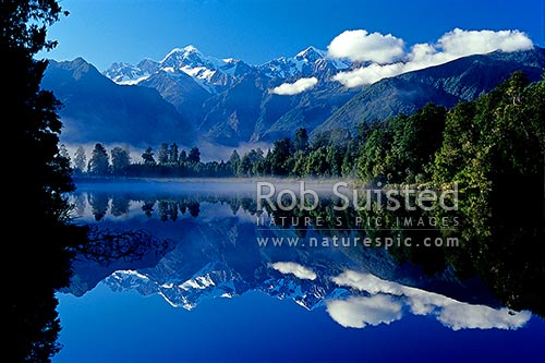 Morning calm reflections on Lake Matheson. Mount (Mt) Cook/Aoraki (right;3754m) and Mount Tasman (left;3498m), Fox Glacier, Westland District, West Coast Region, New Zealand (NZ) stock photo.