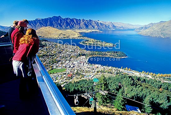 Tourists and visitors viewing The Remarkables Mountains, Lake Wakatipu and Queenstown from the Skyline Gondola, Queenstown, Queenstown Lakes District, Otago Region, New Zealand (NZ) stock photo.