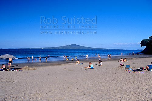 People swimming and playing on Takapuna Beach with Rangitoto Island beyond, Takapuna, North Shore City District, Auckland Region, New Zealand (NZ) stock photo.