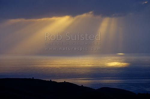 Sunlight breaking through clouds over the eastern Hauraki Gulf from Stoney Batter, Waiheke Island, Waiheke Island, Auckland City District, Auckland Region, New Zealand (NZ) stock photo.