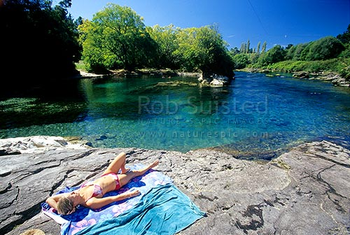 Summer swimming and woman sunbathing at the Waikato River near Taupo, Taupo, Taupo District, Waikato Region, New Zealand (NZ) stock photo.