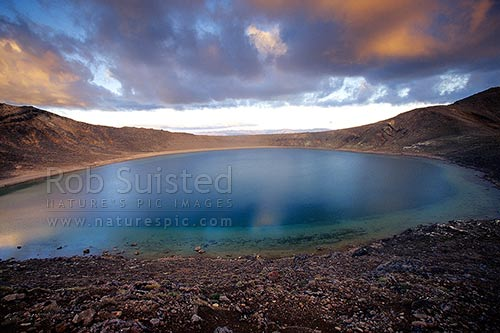 The volcanic Blue Lake reflecting the sunset over Mount Tongariro. Tongariro crossing great walk tramping track, Tongariro National Park, Taupo District, Waikato Region, New Zealand (NZ) stock photo.