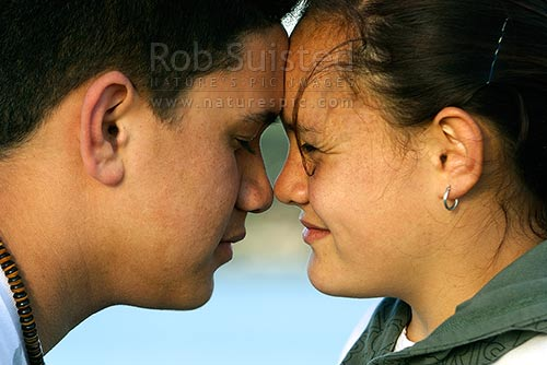 Two Maori teenagers greeting each other with the traditional Maori welcome, a hongi, the pressing together of noses. Formal, New Zealand (NZ) stock photo.