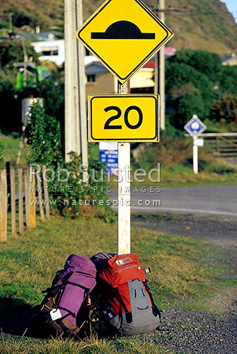 Tramping / hiking packs leaning against road sign, Ngawi, South Wairarapa District, Wellington Region, New Zealand (NZ) stock photo.