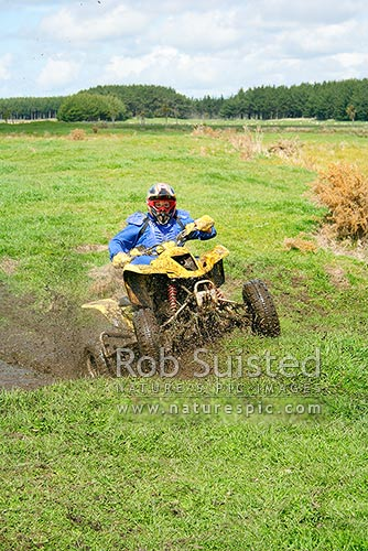 Quad bike racer in muddy bog. Quad bike riding. Motorcycle racing, Foxton, New Zealand (NZ) stock photo.