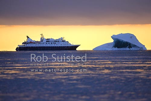 The expedition ship MV Orion in Terra Nova Bay at sunset, behind a green iceberg. Sea freezing to grease ice, Ross Sea, Antarctica District, Antarctica Region, Antarctica stock photo.