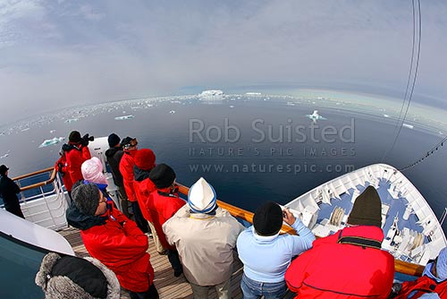Passengers watching pack ice and icebergs from Expedition ship MV. 66 degrees South. Approx 66º 2' S 141º34' E, Open southern ocean. Fish-eye lens, Commonwealth Bay, George V Land, Antarctica District, Antarctica Region, Antarctica stock photo.