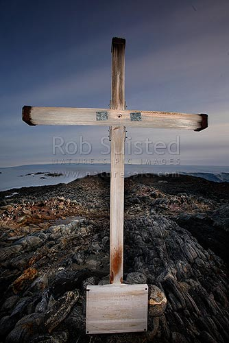 1913 Memorial Cross for Belgrave Ninnis and Xavier Mertz, Azimuth Hill, Mawson's Huts, Cape Denison. Adelie Penguins (Pygoscelis adeliae), Commonwealth Bay, George V Land, Antarctica Region, Antarctica stock photo.