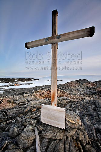 1913 Memorial Cross for Belgrave Ninnis and Xavier Mertz, Azimuth Hill, Mawson's Huts behind, Cape Denison, Commonwealth Bay, George V Land, Antarctica Region, Antarctica stock photo.