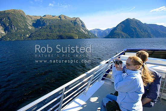 Tourists enjoying the scenery near First Arm of Doubtful Sound, Fiordland. Real Journeys tour, Fiordland, Southland District, Southland Region, New Zealand (NZ) stock photo.