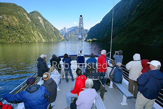 Tourists enjoying the view in Doubtful Sound, Hall Arm from a fiord boat cruise. Real Journeys, Fiordland National Park, Southland District, Southland Region, New Zealand (NZ) stock photo.