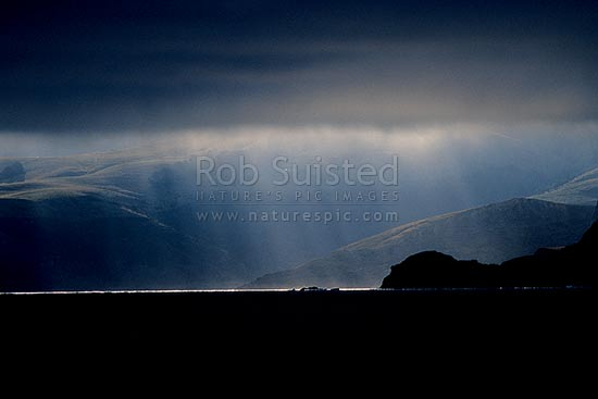 Dramatic sun lighting on the coast and landscape of Banks Peninsula from a breaking storm, Banks Peninsula, Christchurch City District, Canterbury Region, New Zealand (NZ) stock photo.