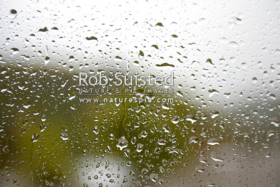 Rain drops and water on window pane. Wet raining weather, New Zealand (NZ) stock photo.