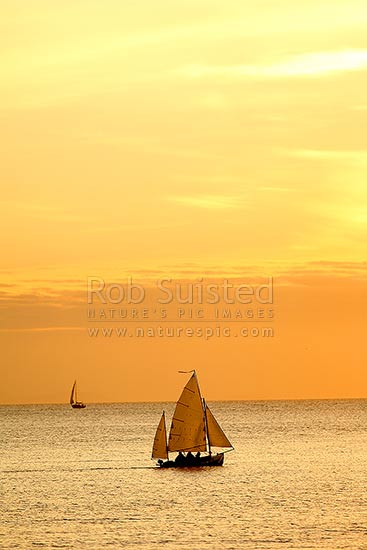 Small sailing ketch and yacht in Plimmerton Harbour at twilight. South Island (faint) behind, Plimmerton, Porirua City District, Wellington Region, New Zealand (NZ) stock photo.