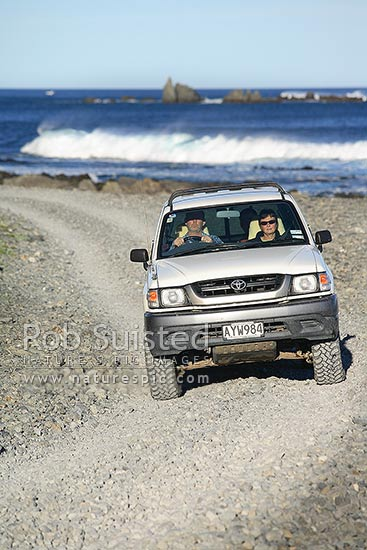 Four wheel drive (4WD) vehicle driving on gravel beach road on Wellington South Coast, Cook Strait beyond, Wellington, New Zealand (NZ) stock photo.