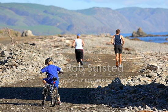 Family exercising with parents jogging and child biking - cycling around coast. Catching up, Plimmerton, Porirua City District, Wellington Region, New Zealand (NZ) stock photo.