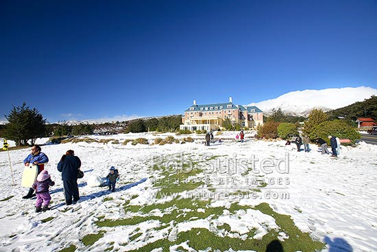 Tourists and families enjoying the snow in front of The Grand Chateau at Whakapapa, below Mount (Mt) Ruapehu (2797m asl), Tongariro National Park, Ruapehu District, Manawatu-Wanganui Region, New Zealand (NZ) stock photo.
