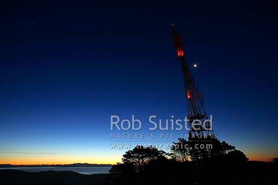 Radio and TV transmitter tower at night with moon on Mount (Mt) Kaukau. Cook Strait beyond, Wellington, Wellington City District, Wellington Region, New Zealand (NZ) stock photo.