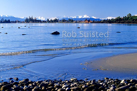 Calm winter reflections on Lake Te Anau and township, with snowy Livingstone Mountains behind, Te Anau, Southland District, Southland Region, New Zealand (NZ) stock photo.