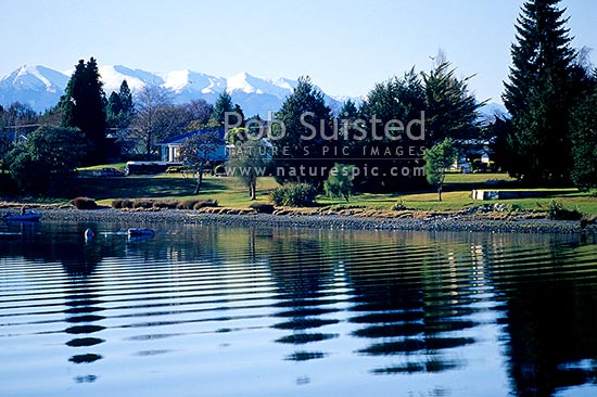 Calm winter reflections on Lake Te Anau and township, with snowy Murchison Mountains behind, Te Anau, Southland District, Southland Region, New Zealand (NZ) stock photo.