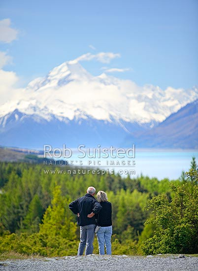 Man and woman tourist admiring view of Aoraki / Mount Cook, beyond Lake Pukaki, Aoraki / Mount Cook National Park, MacKenzie District, Canterbury Region, New Zealand (NZ) stock photo.