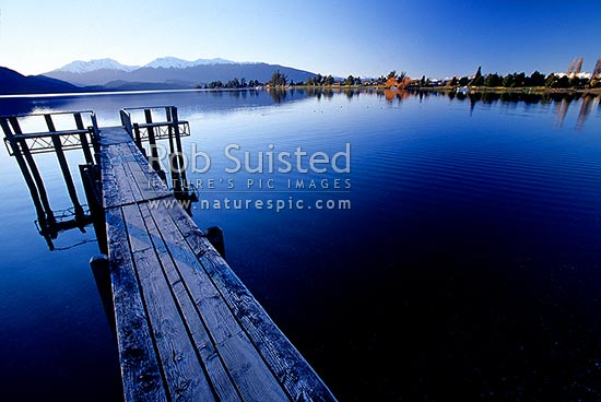 Calm winter reflections on Lake Te Anau and jetty. Snowy Murchison Mountains behind., Te Anau, Southland District, Southland Region, New Zealand (NZ) stock photo.