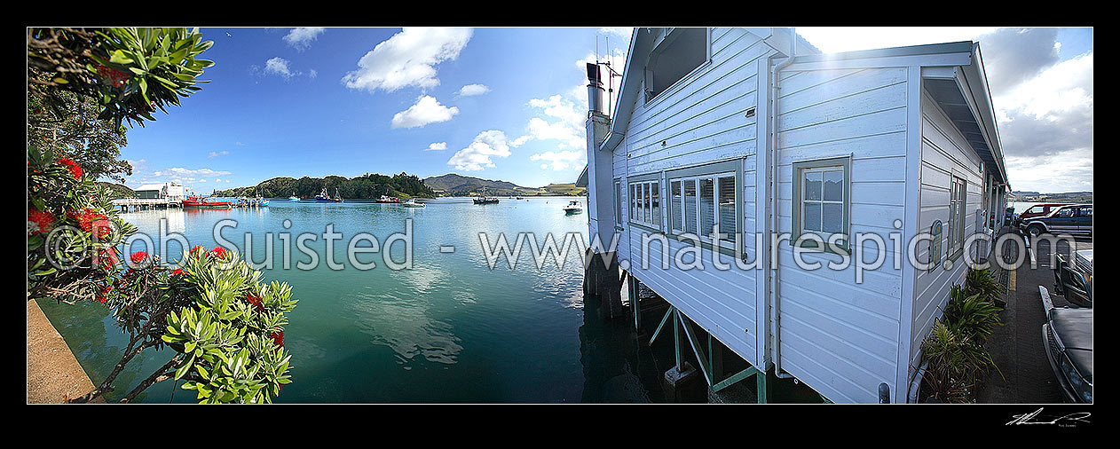 Image of Mangonui harbour, wharf and historic building, with flowering pohutukawa flowers over water, Mangonui, Far North District, Northland Region, New Zealand (NZ) stock photo image