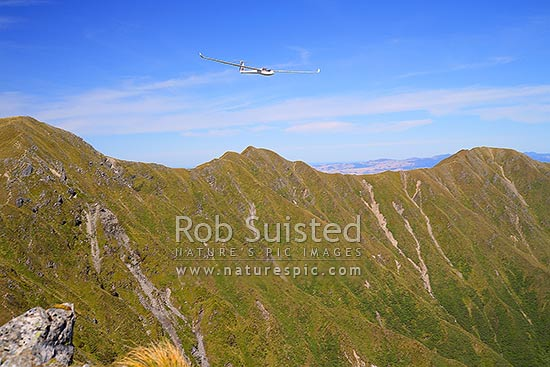 Glider plane flying, soaring or gliding high above Mount (Mt) Hector and memorial cross in the Tararua Ranges, Tararua Forest Park, Kapiti Coast District, Wellington Region, New Zealand (NZ) stock photo.