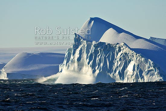 Tabular icebergs eroded and tilted in sea. Polar ice cap beyond, Terre Adelie Land, Antarctica stock photo.