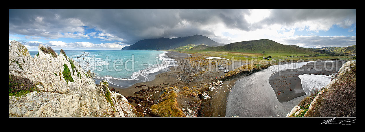 Image of Whawanui River entering the sea at White Rock beach, with moody Aorangi Mountains (Haurangi Forest Park) and Cape Palliser beyond., White Rock, Wairarapa, South Wairarapa District, Wellington Region, New Zealand (NZ) stock photo image