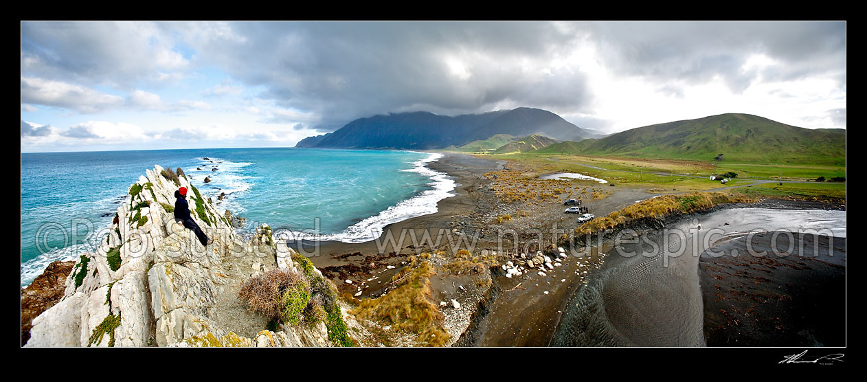 Image of Person above the Whawanui River entering sea at White Rock beach, with moody Aorangi Mountains (Haurangi Forest Park) and Cape Palliser beyond., White Rock, Wairarapa, South Wairarapa District, Wellington Region, New Zealand (NZ) stock photo image