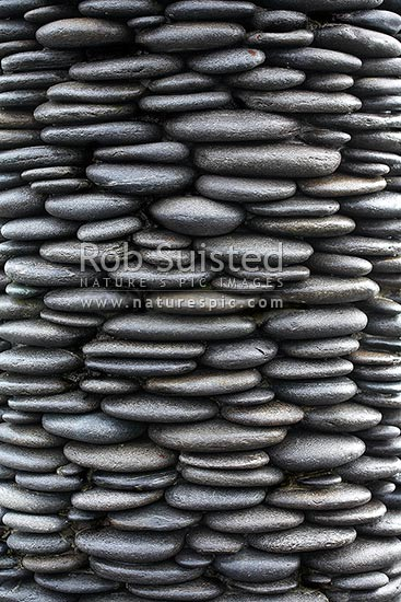 Repeating pattern of stacked river stones or rocks in cylinder shaped column, New Zealand (NZ) stock photo.