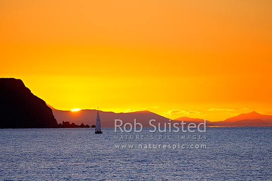 Sunset over the South Island on the far side of Cook Strait from Mana Island (left) and homeward bound sail boat yacht into Paremata, Plimmerton, Porirua City District, Wellington Region, New Zealand (NZ) stock photo.