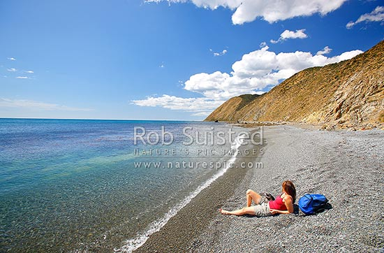 Woman walker enjoying the sun and sea at remote Opau Bay Beach on the Makara Walkway, Makara Beach, Wellington City District, Wellington Region, New Zealand (NZ) stock photo.