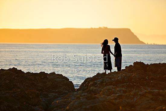 Young couple in love holding hands in sunset on rocky shore at beach, Plimmerton, Porirua City District, Wellington Region, New Zealand (NZ) stock photo.