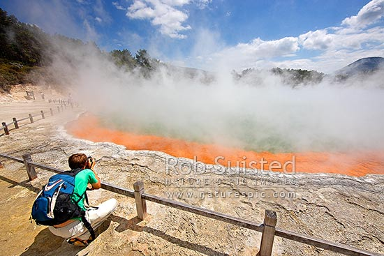 Tourist visitor photographing the famous coloured hotspring 'Champagne Pool' and sintered terrace, Waiotapu Geothermal Area. Wai-o-tapu, Rotorua, Rotorua District, Bay of Plenty Region, New Zealand (NZ) stock photo.