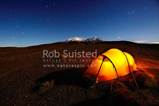 Night time exposure of tent camp on the Round the Mountain Track of Mount Ruapehu in moonlight - summit behind. Rangipo Desert. Star trails above, Mt Ruapehu, Ruapehu District, Manawatu-Wanganui Region, New Zealand (NZ) stock photo.