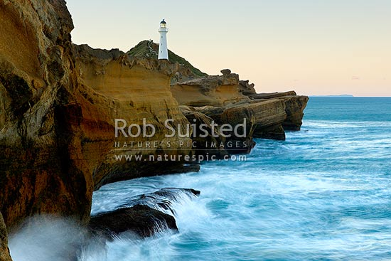 Castlepoint Reef with waves surging against cliffs at dusk. Castlepoint Lighthouse (1913) and scenic reserve. Sea movement blurred, Castlepoint, Masterton District, Wellington Region, New Zealand (NZ) stock photo.