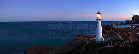 Castlepoint Lighthouse (1913) at dusk, looking across reef, sandbar and lagoon towards Castle rock (162m). Castlepoint scenic reserve. Panorama, Castlepoint, Masterton District, Wellington Region, New Zealand (NZ) stock photo.