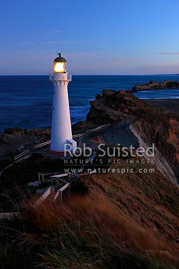 Castlepoint Lighthouse (1913) at dusk, looking across reef, sandbar and lagoon. Castlepoint scenic reserve, Castlepoint, Masterton District, Wellington Region, New Zealand (NZ) stock photo.