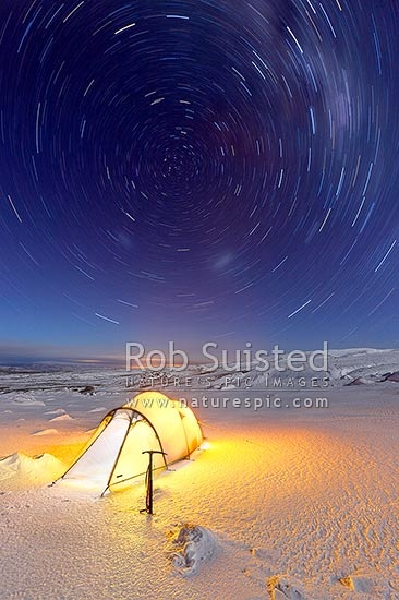 Winter tent camp on the Round the Mountain Track of Mount Ruapehu in moonlight and snow. Rangipo Desert. Time exposure star trails orbiting around the southern celestial pole, Tongariro National Park, Ruapehu District, Manawatu-Wanganui Region, New Zealand (NZ) stock photo.
