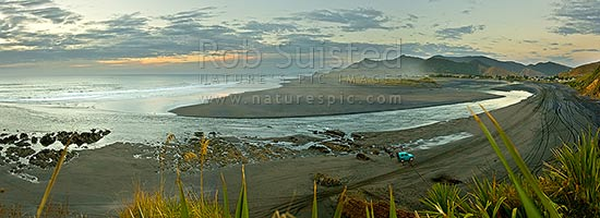 Marokopa beach and river mouth. Wild west coast at sunset with 4wd and tracks on beach. Black iron sand. Looking north from river mouth with town at right. Moody panorama, Marokopa, Waitomo District, Waikato Region, New Zealand (NZ) stock photo.