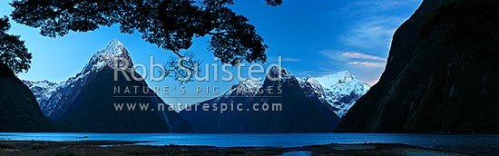 Mitre Peak in Milford Sound fiordland. Mitre Peak left (1683m), Stirling Falls centre, The Lion (1302m) and Mt Pembroke (2015m) right centre. Panorama at dawn, Milford Sound, Fiordland National Park, Southland District, Southland Region, New Zealand (NZ) stock photo.