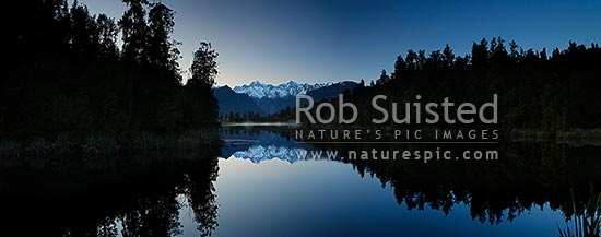 Lake Matheson. Pre-dawn morning calm reflections on lake with Aoraki / Mount Cook (right;3754m) and Mount Tasman (left;3498m). Morning mist. Panorama, Westland National Park, Westland District, West Coast Region, New Zealand (NZ) stock photo.