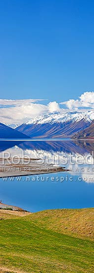 Lake Hawea on a perfect calm spring/winter day reflecting the surrounding snowy ranges. Looking towards head of lake. Vertical panorama, Hawea, Queenstown Lakes District, Otago Region, New Zealand (NZ) stock photo.