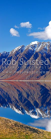 Lake Hawea on a perfect calm spring/winter day reflecting the surrounding snowy ranges. Vertical panorama, Hawea, Queenstown Lakes District, Otago Region, New Zealand (NZ) stock photo.
