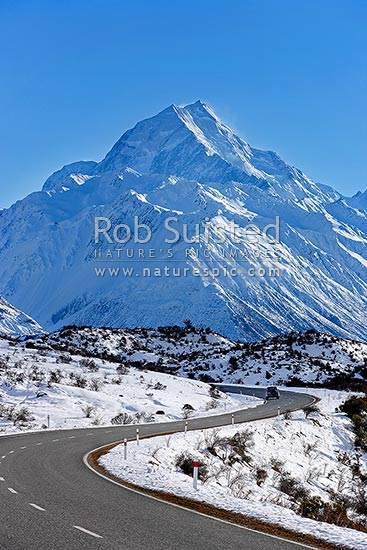 Aoraki / Mount Cook (3754m) and Tasman Valley in heavy winter snow. Car vehicle on State Highway 80 road to Hermitage, Aoraki / Mount Cook National Park, MacKenzie District, Canterbury Region, New Zealand (NZ) stock photo.