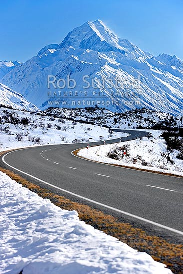 Aoraki / Mount Cook (3754m) and Tasman Valley in heavy winter snow. State Highway 80 road to Hermitage below, Aoraki / Mount Cook National Park, MacKenzie District, Canterbury Region, New Zealand (NZ) stock photo.